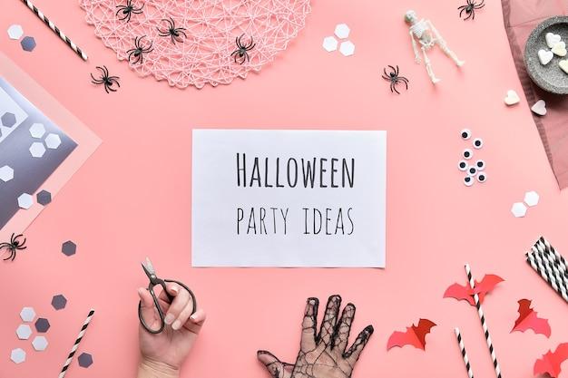 Testo di idee del partito di halloween sulla pagina bianca tenuto in mano. lay piatto con forbici e decorazioni su carta rosa