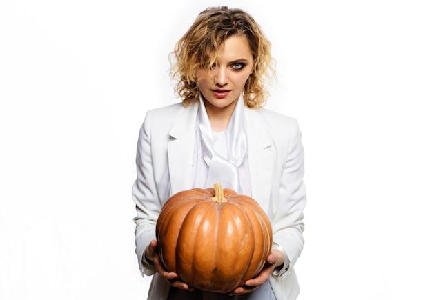 Festa di halloween. strega sexy con zucca. zucche magiche. ragazza sorridente con grande zucca. cibo tradizionale.