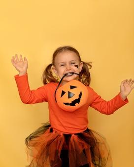 Festa di halloween sorridente bambino emotivo tenere caramelle zucca secchio isolato giallo