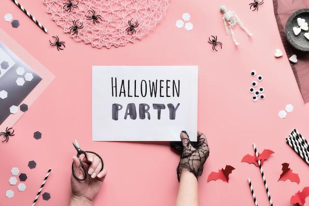 Testo del partito di halloween sulla pagina bianca tenuto in mano. lay piatto con decorazioni in bianco e nero, pagina della stretta della mano con testo