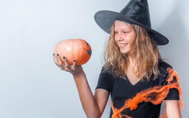 Ritratto di halloween di adolescente con zucca in costume