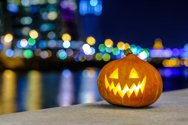 Zucca di halloween sullo sfondo della città notturna con luci colorate sfocate