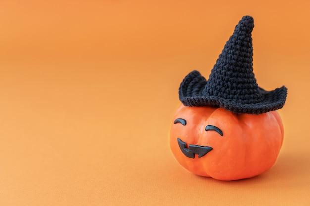 Zucca di halloween con cappello nero con faccia buffa su sfondo arancione