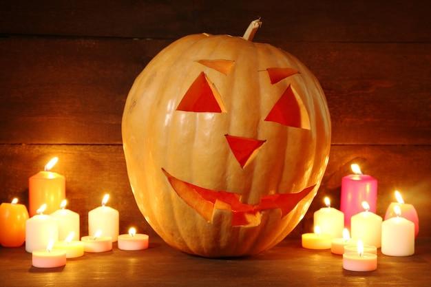 Zucca di halloween e candele, su legno