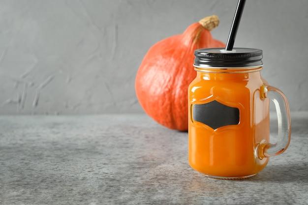 Cocktail della zucca di halloween con lo spazio della copia sul barattolo di vetro su gray