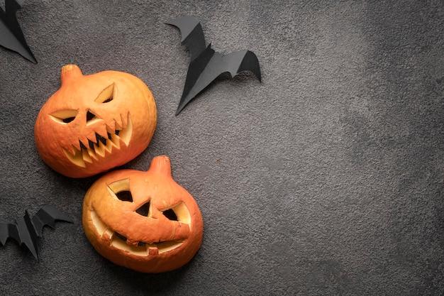 Zucca di halloween flatlay, copia spazio foto su sfondo scuro modello. due spaventose zucche autunnali con la testa di jack, un mockup con un sorriso minaccioso e un sorriso malvagio.