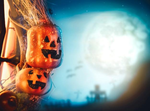 La zucca di halloween e il cimitero hanno sfocato lo sfondo nella notte di luna piena con lo spazio della copia, concetto di celebrazione di halloween