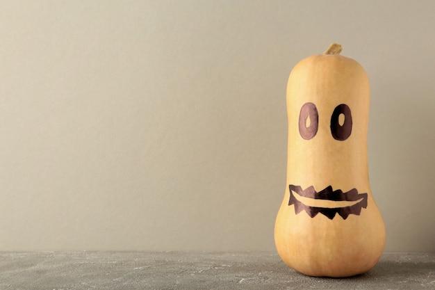 Zucca di halloween, jack spaventoso su sfondo grigio