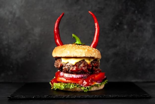 Hamburger a forma di zucca di halloween con corna di peperone rosso sul muro di pietra