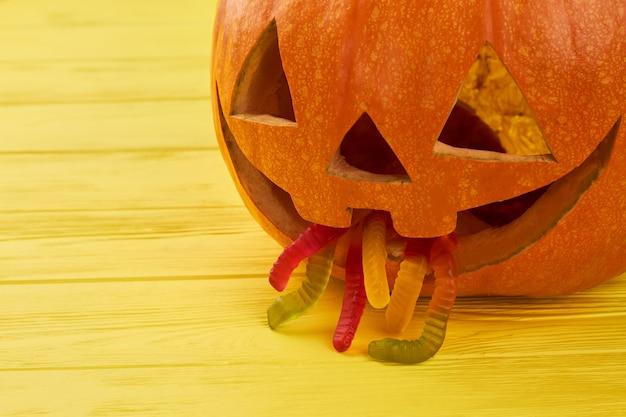 Zucca di halloween con i vermi di gelatina in bocca che vomitano zucca su fondo di legno giallo