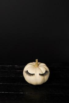 Zucca di halloween con trucco ciglia finte su sfondo nero. concetto di stagione delle vacanze di halloween