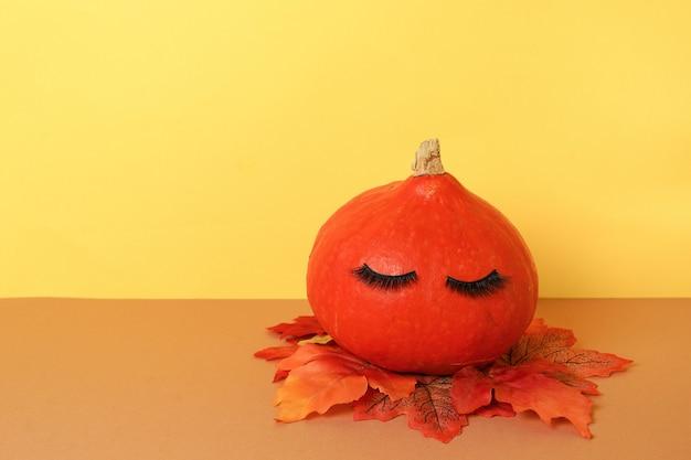Zucca di halloween con ciglia finte di trucco. priorità bassa di concetto di stagione di festa di halloween