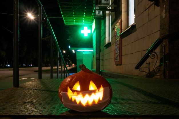 Zucca di halloween con una maschera protettiva sul viso sullo sfondo di una croce da farmacia