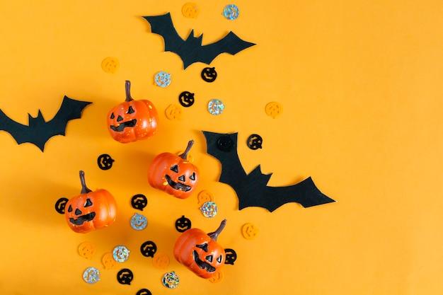 Zucche di halloween, pipistrelli, oggetti per feste distesi su sfondo arancione. vista dall'alto, copia dello spazio.