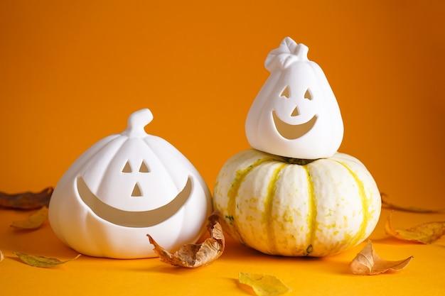 Zucche di halloween, foglie secche su sfondo giallo. concetto di halloween. composizione autunnale.