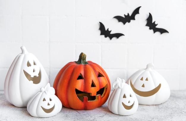 Zucche di halloween e decorazioni jack o lantern contro un muro bianco con pipistrelli.