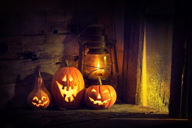 Zucche di halloween e lanterna in una vecchia casa vicino alla finestra dove risplende la luce della luna.