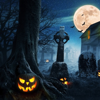 Zucche di halloween vicino a un albero in un cimitero con una casa spaventosa. sfondo di halloween di notte nella foresta con luna e pipistrelli.