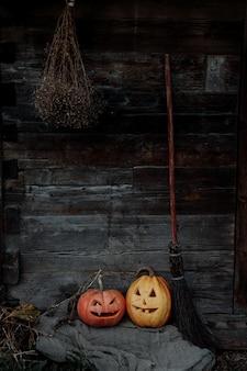 Zucche di halloween con una scopa contro un vecchio muro di legno