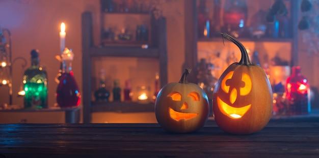 Zucche di halloween con candele e pozioni magiche di notte al coperto