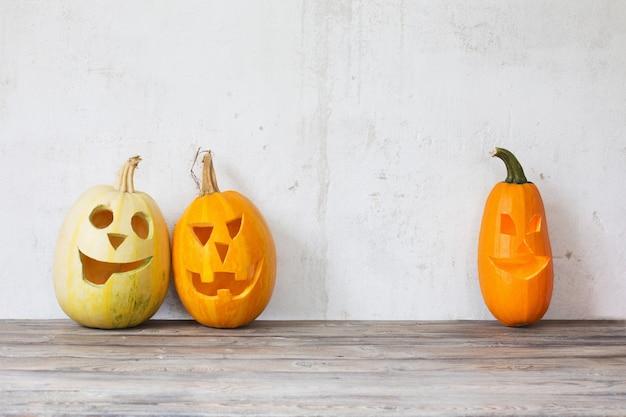 Zucche di halloween sulla tavola di legno sul vecchio muro bianco del fondo