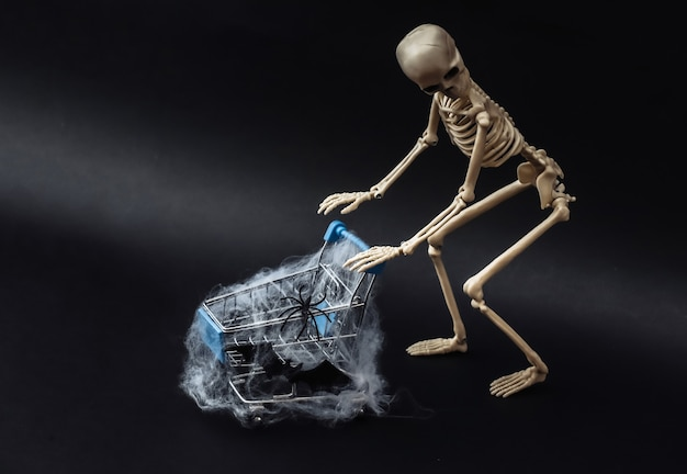 Halloween, tema spaventoso. scheletro falso e carrello della spesa in web su fondo nero.