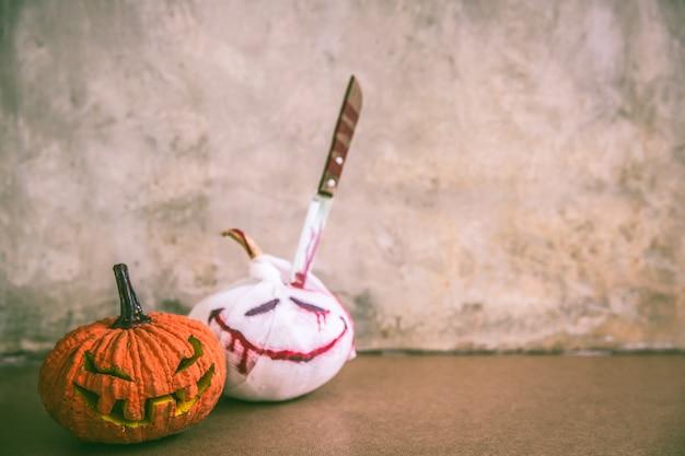 Zucca spettrale di halloween e della mummia di halloween con il fondo grigio del muro di cemento del sottotetto