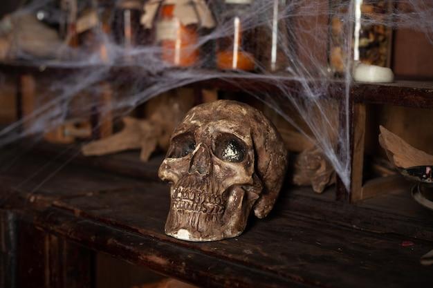 Superficie di halloween mensole con strumenti alchemici bottiglia di ragnatela teschio con candele velenose area di lavoro di witcher stanza di scarry