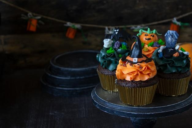 Simboli di halloween, preparazione per la vacanza. cupcakes di zucca arancione e decorazioni in legno.