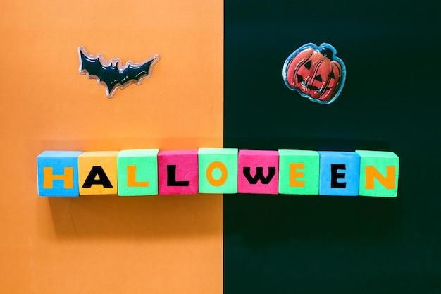 Testo di halloween con pipistrello nero e zucca