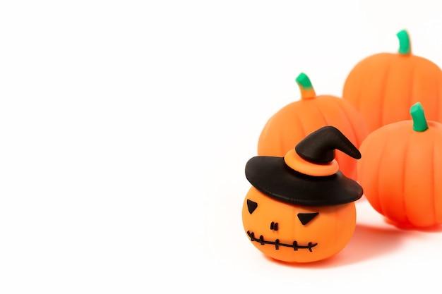 Zucche giocattolo di halloween. jack-o'-lantern in cappello nero con zucche intorno su priorità bassa bianca con lo spazio della copia.