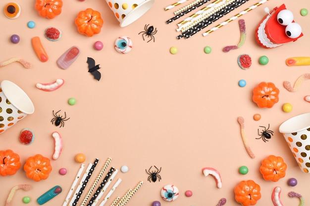 Dolcetti di halloween su uno sfondo arancione. varie caramelle con un posto per il testo.