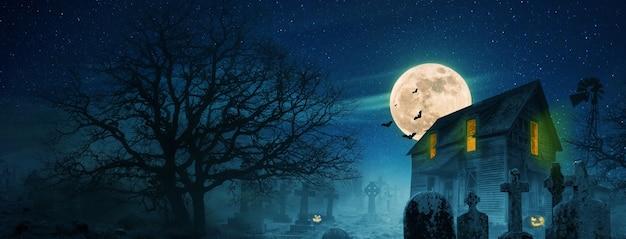Carta da parati di halloween. casa spaventosa vicino a un cimitero con alberi, luna piena, pipistrelli, nebbia e zucche. idee per immagini spettrali di halloween