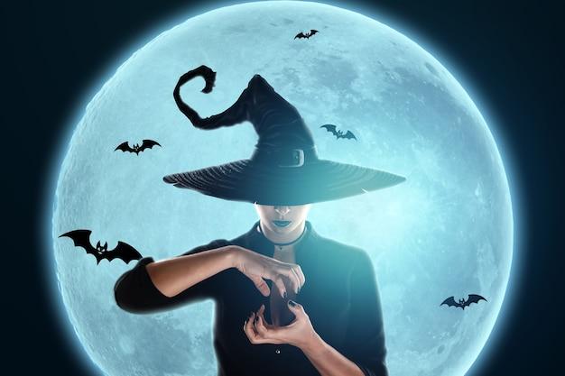 La ragazza della strega di halloween evoca sullo sfondo della luna. bella giovane donna in un cappello da strega.