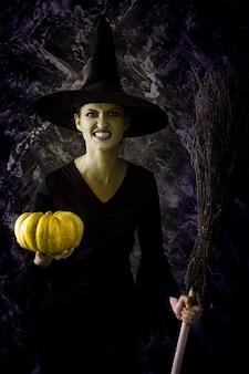 Strega di halloween che tiene una zucca e una scopa. donna vestita come una fata strega