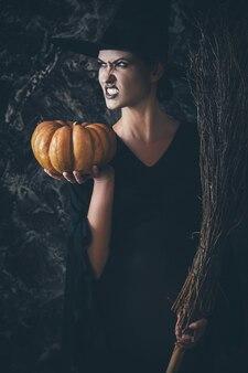 Strega di halloween che tiene una zucca e una scopa