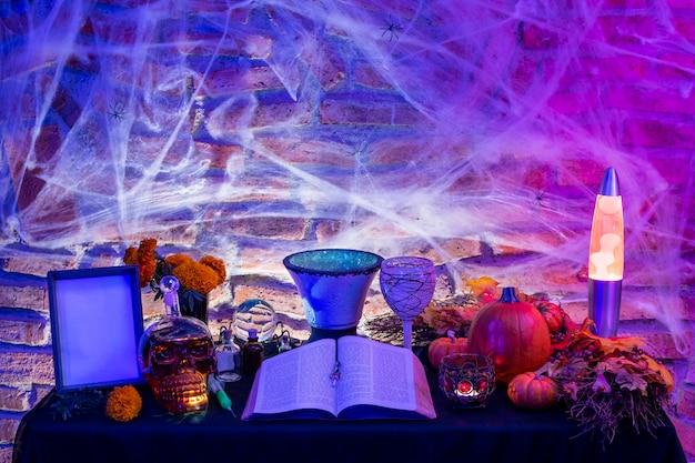 Tavolo della strega di halloween, altare con oggetti magici, libro antico per un incantesimo, candele accese e zucca