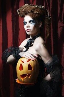 Strega di halloween con la zucca intagliata sopra la tenda rossa