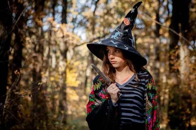 Strega di halloween con un coltello nel bosco.