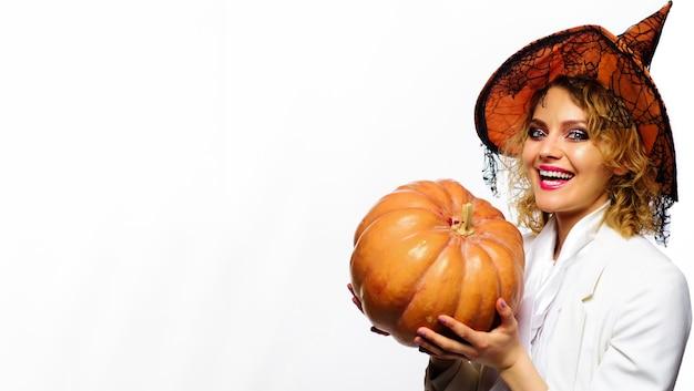 Strega di halloween con la zucca. donna sorridente in costume delle streghe. ragazza di festa di halloween. zucche intagliate.