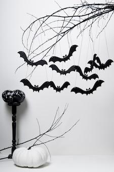 Halloween con pipistrelli neri e zucche su un albero su sfondo bianco