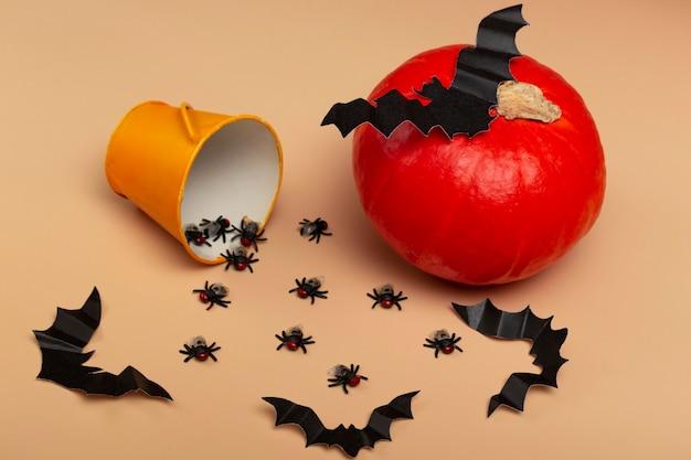 Halloween con zucche, ragni, secchio giallo, mosche e pipistrello su fondo beige. concetto di festa di halloween