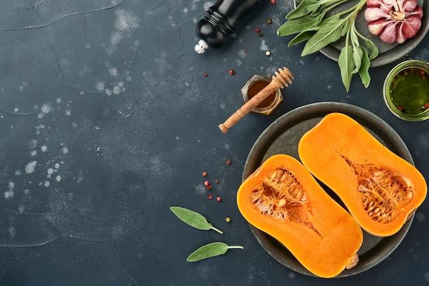 Metà della zucca butternut organica cruda con foglia di salvia, aglio pepe multicolore, miele, sale e pepe su sfondo nero di ardesia, pietra o cemento. sfondo di cibo. vista dall'alto con copia spazio.