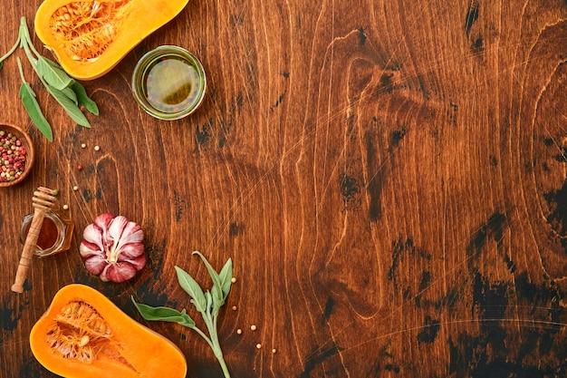 Metà della zucca butternut organica cruda con foglia di salvia, aglio pepe multicolore, miele, sale e pepe su fondo di legno vecchio. sfondo di cibo. vista dall'alto con copia spazio.