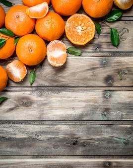 Metà e mandarini interi. sullo sfondo di legno