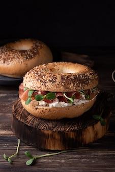 Bagel al prosciutto per colazione su fondo di legno scuro, panino con ricotta, prosciutto e microgreens, stile rustico.
