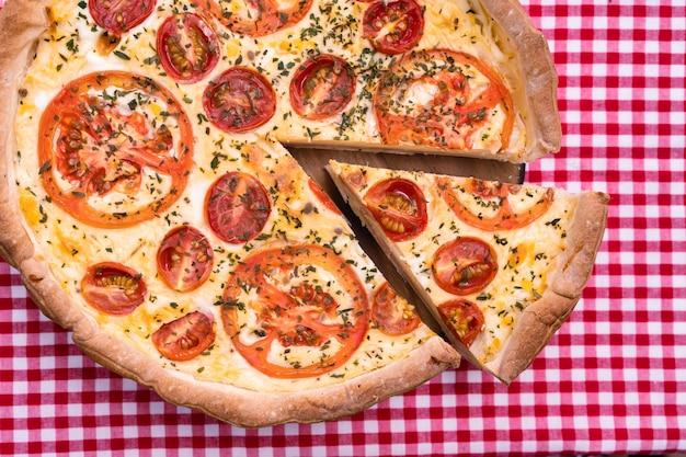 Torta di prosciutto e formaggio con pomodoro o quiche lorraine con una porzione tagliata e separata dalla torta. cibo domestico, concetto sano