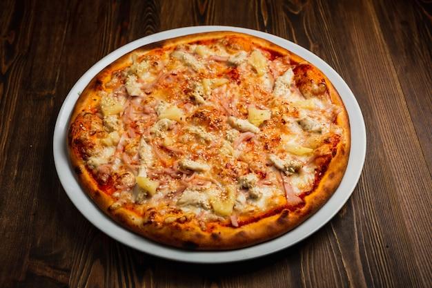 Pizza prosciutto, formaggio, carne di pollo e ananas, fondo in legno, scuro