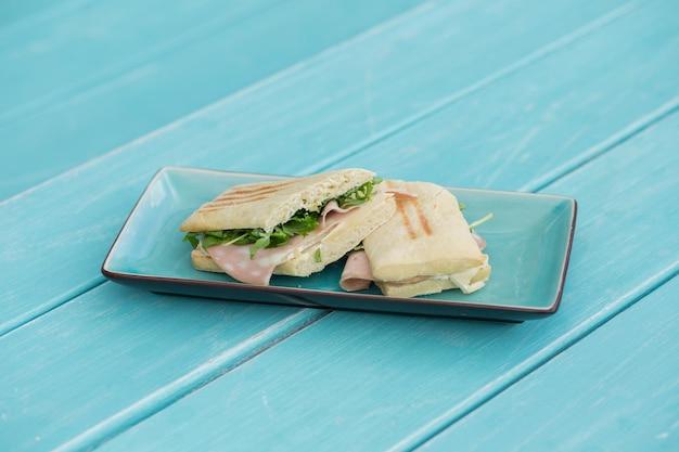 Panino al prosciutto e formaggio nel piatto azzurro sulla tavola di legno azzurro
