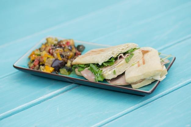 Panino al prosciutto e formaggio con contorno sul piatto azzurro sul tavolo di legno azzurro
